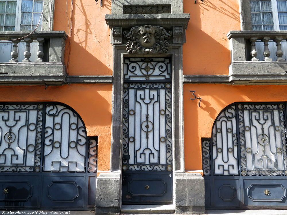 An orange exterior wall with wrought iron window coverings in Mexico City