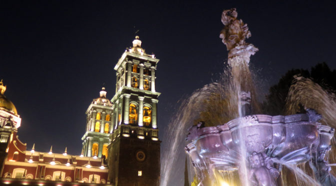 A view of the Puebla Cathedral and a fountain lit up at night.