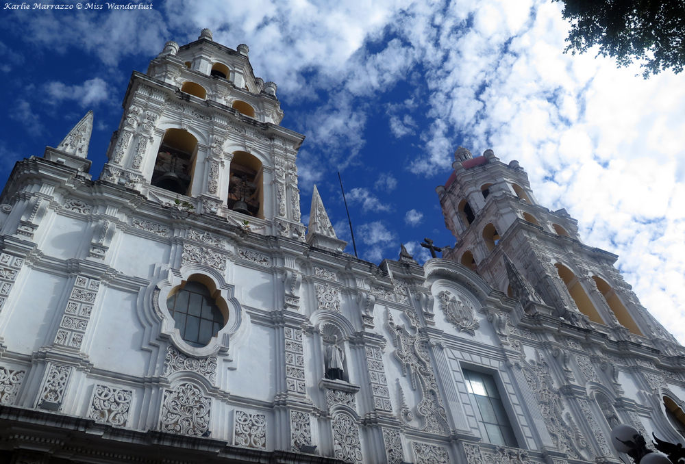 Looking up at a white church against a blue sky in Puebla, Mexico.