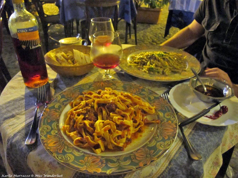 A heaping plate of pasta in tomato sauce, a basket of bread and a bottle of rose wine in Cosenza, Italy.