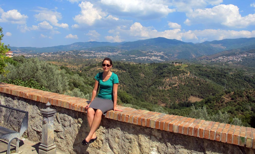 A brown-haired girl in a green top and grey skirt sits on a brick ledge overlooking the hills of Southern Italy.
