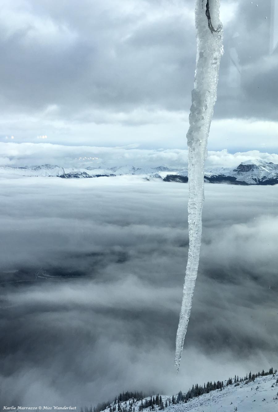A large icicle hangs in the foreground with the Rocky Mountains shrouded in clouds in the background.