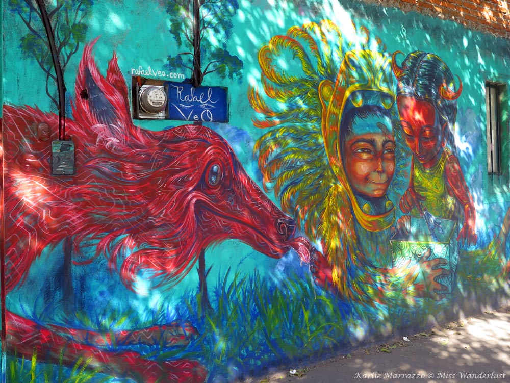 Vibrant street art in Mexico City depicting a bright red dog and people against a turqoiuse background.