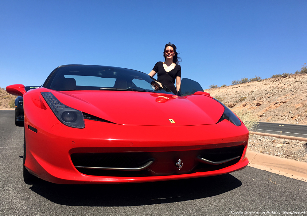 A brunette woman stands beside a red Ferrari 458 Spider in the Nevada desert