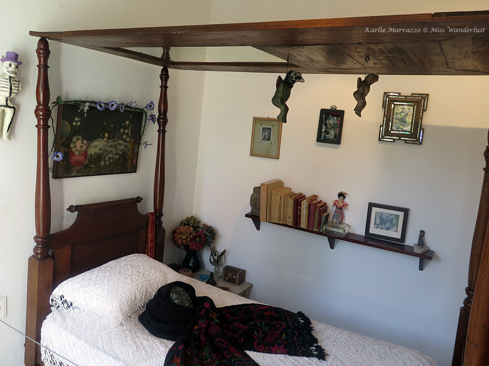 A small bed with Frida Kahlo's desk mask laid upon it. A small shelf and framed pictures on the wall.