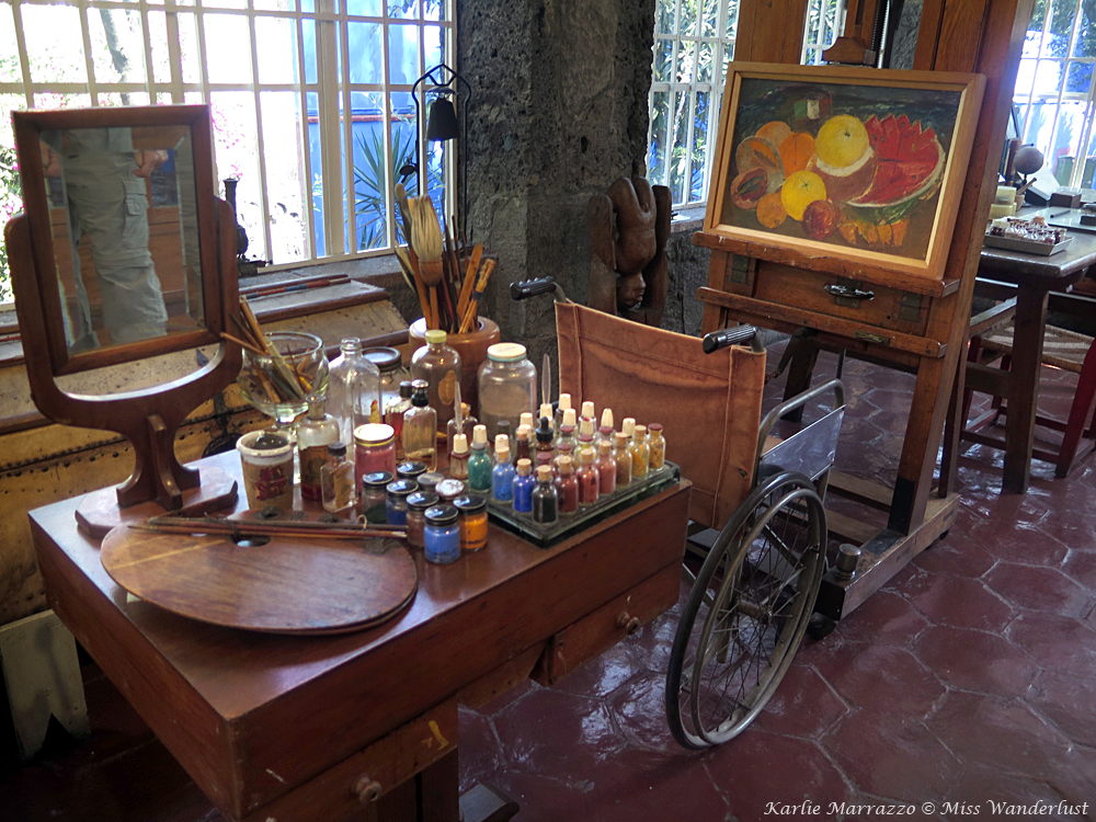 An easel, a wheelchair, and a table full of paints and art supplies in Frida Kahlo's art studio.