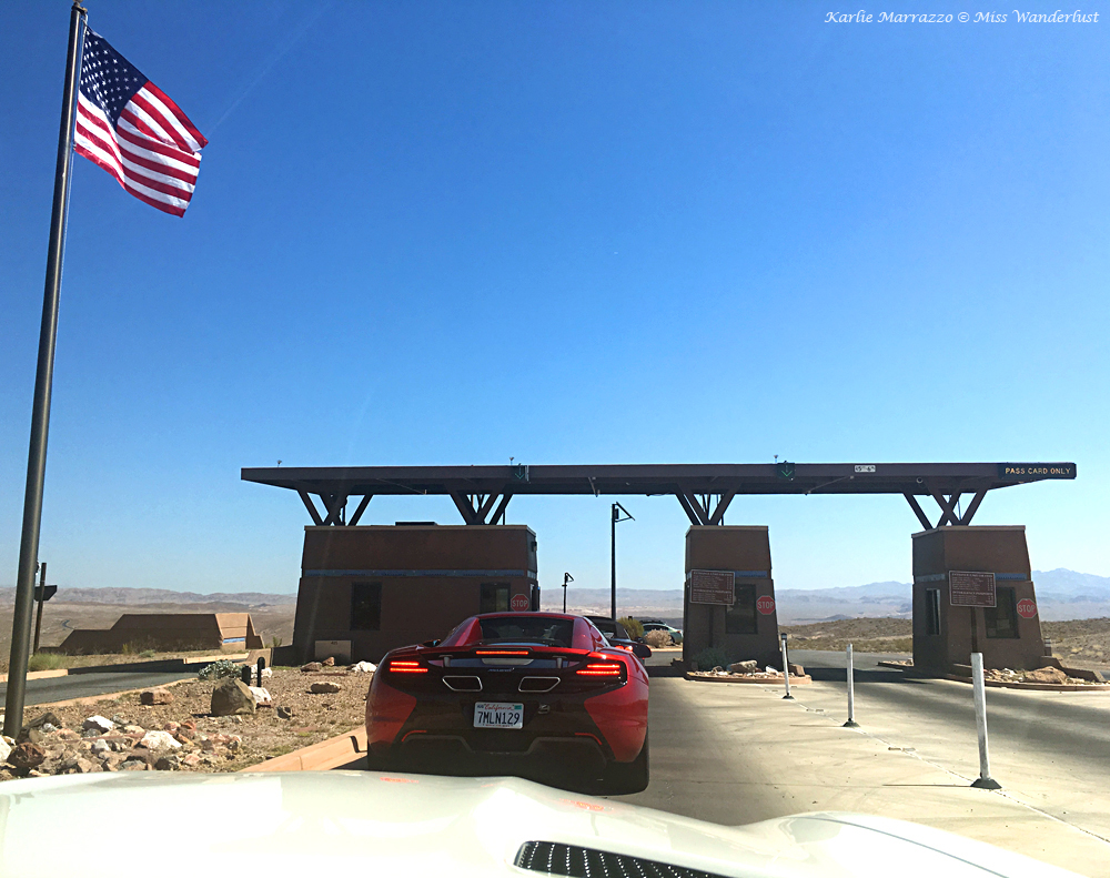 A McLaren 12C Spider sits at the entrance to Lake Mead National Recreation Area with an American flag