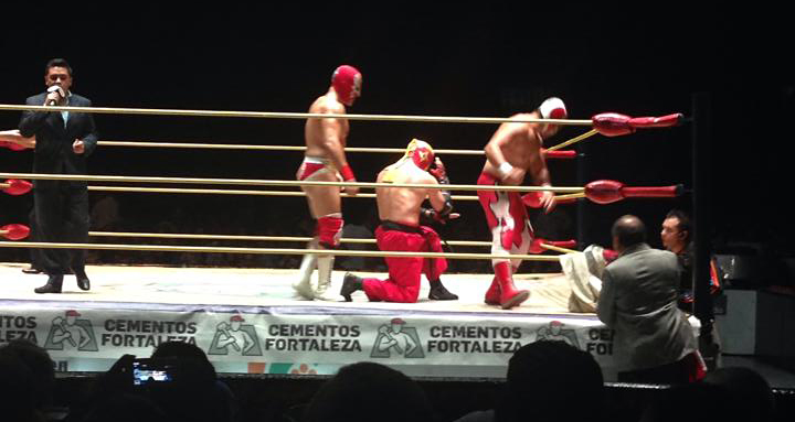 Three Mexican wrestlers in the ring at a lucha libre match in Mexico City.