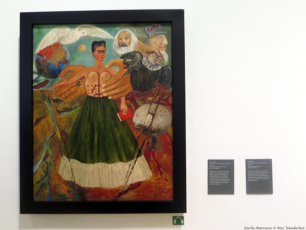 A Frida Kahlo painting depicting the artist wearing a dress and holding a book. A dove and the head of Karl Marx float behind her.