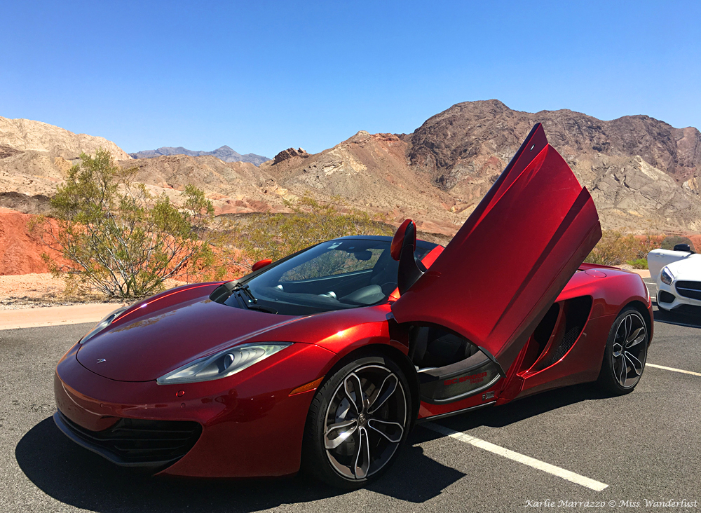 A purple McLaren 12C Spider with the butterfly door open in the Nevada desert