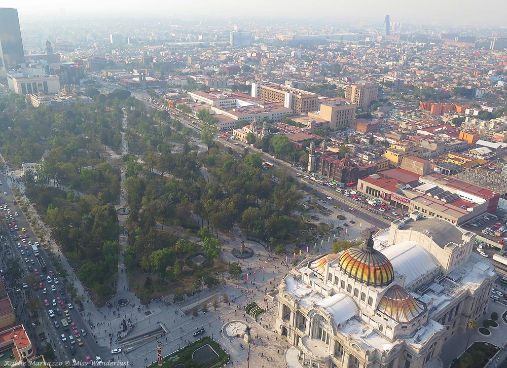 A view over Mexico City from the top of the Torre Latinoamericano. Palacio Bellas Artes is in the foreground beside a green park, while the ccity sprawls behind it.