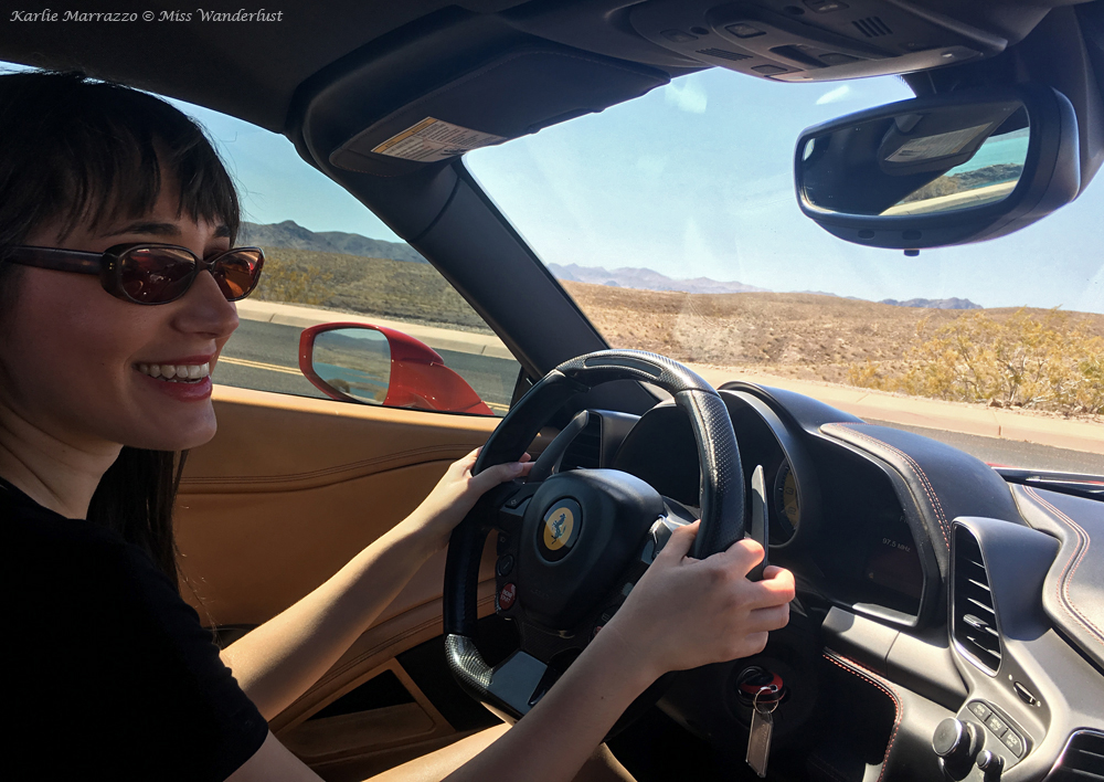 A brown haired woman smiles behind the wheel of a Ferrari 458 Spider