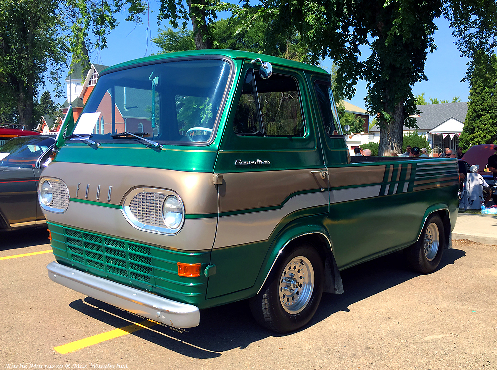 A green and silver 1960s Ford Econoline truck shown from the front