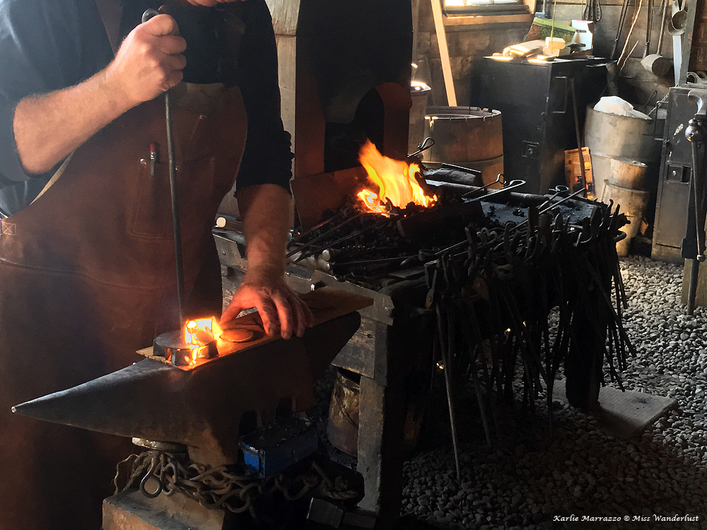 A close up shot of a blacksmith's hands working over an open flame