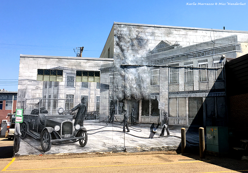 A black and white mural depicting life in the early 20th century in the town of Lacombe