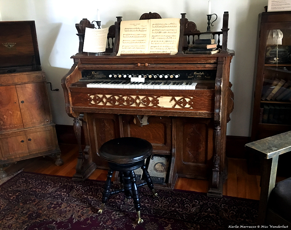 A turn of the century pump organ with sheet music and a stool