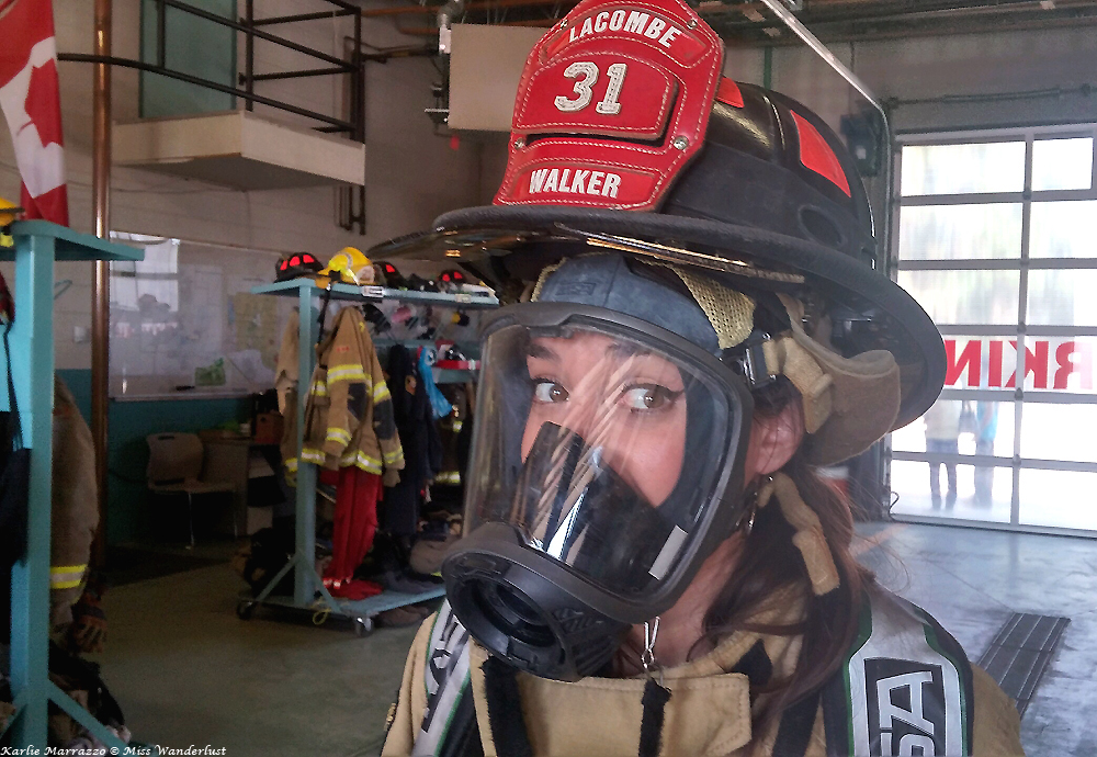 A woman with brown eyes wears firefighting equipment, helmet and an oxygen mask