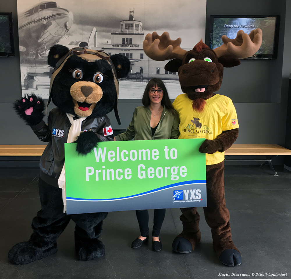 A brunette woman stands between two mascots, a bear and a moose
