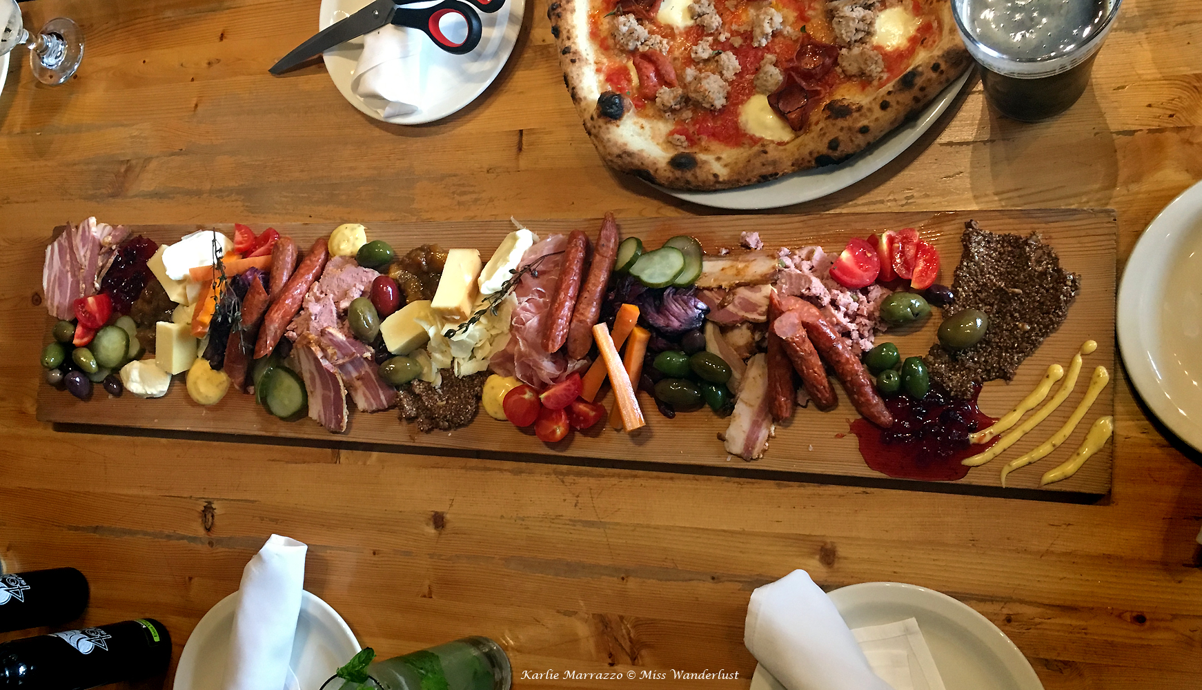 An aerial view of a charcuterie board covered with cured meats, cheeses, pickled vegatables and olives, set on a wooden table