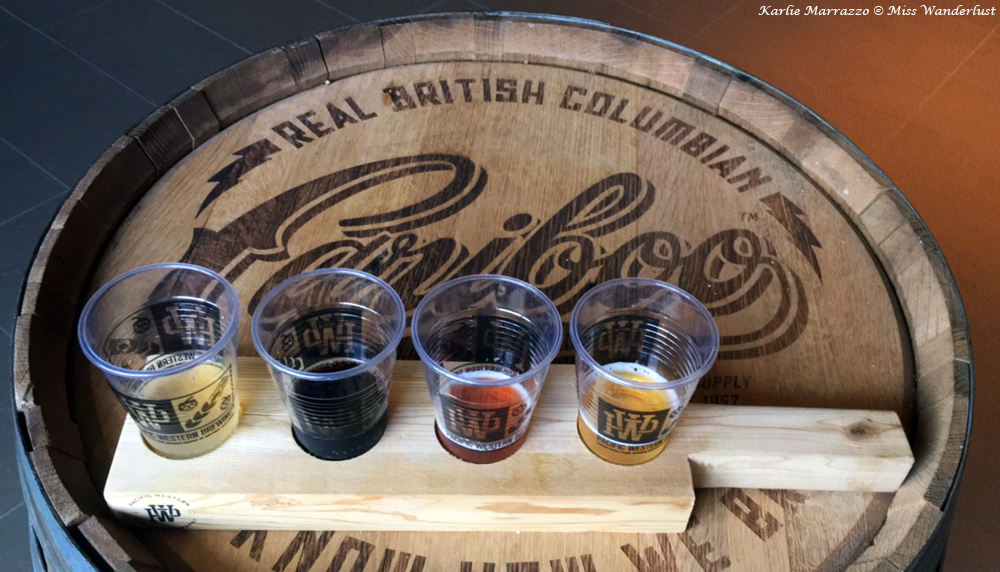 Four small plastic cups hold different types of beer, sitting atop a wooden barrel with the brewery logo on it