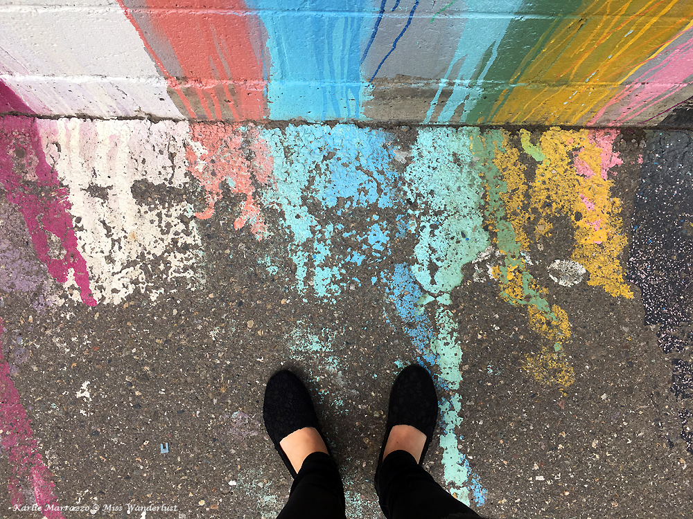 A pair of feet standing on concerte with splashes of blue, red, pink, green and yellow paint spilling down the wall in front of them