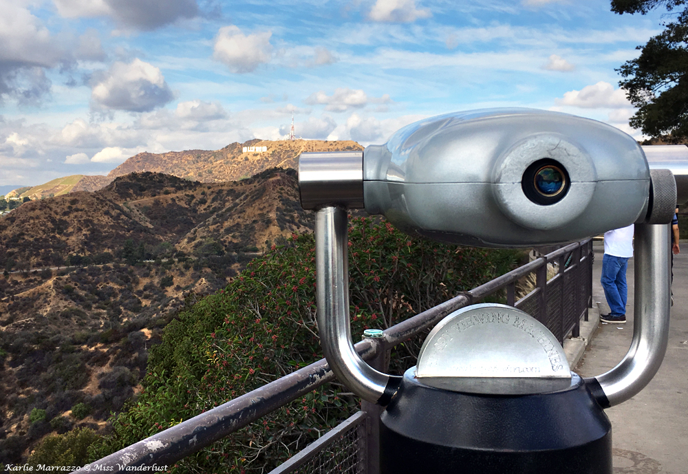 A close up shot of a scenery view finder, with the Hollywood hills and Hollywood sign in the distance and a cloudy blue sky