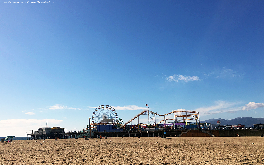 A roller coaster and ferris wheel sit on a pier, with a beach in the foreground against a blue sky