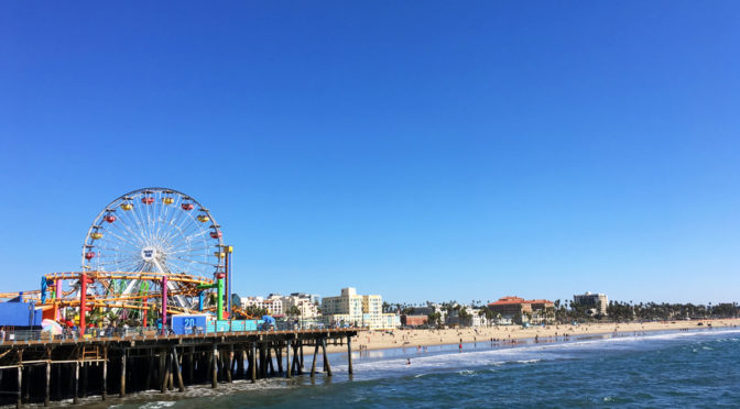 A view from the water of Santa Monica Pier, with roller coaster, blue sky and beach