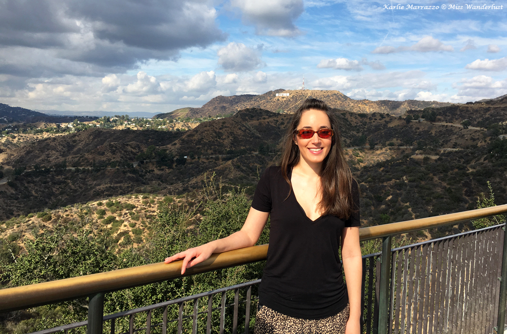 A brunette woman in sunglasses stands in the foreground in front of the Hollywood Sign