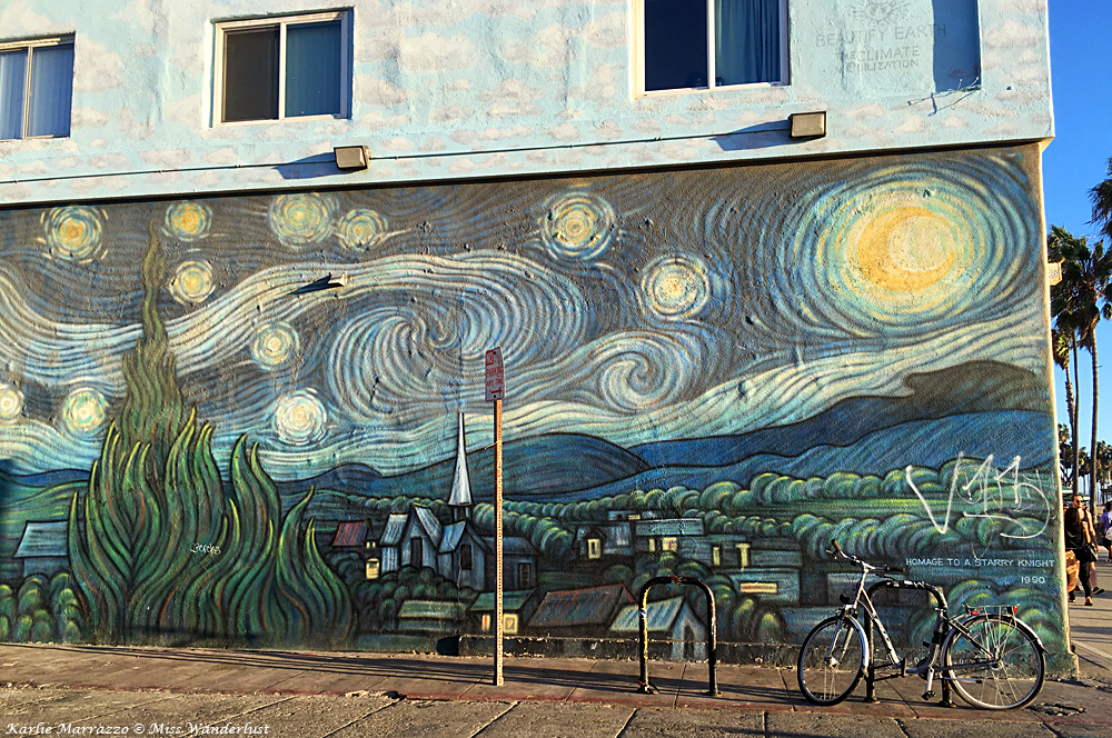 The side of a building with a version of Starry Night by Vincent Van Gogh painted on the side, in blues, greens and yellows. There is a bike in front of the building.