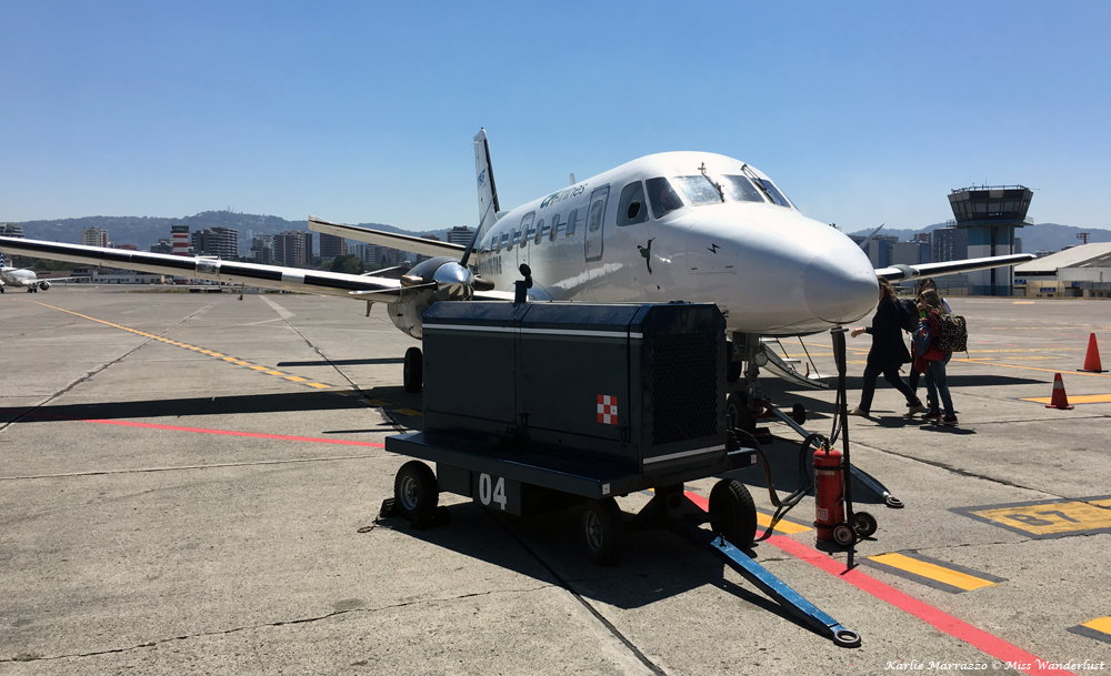 a small twin-turboprop airplane sits on the tarmac at an airport