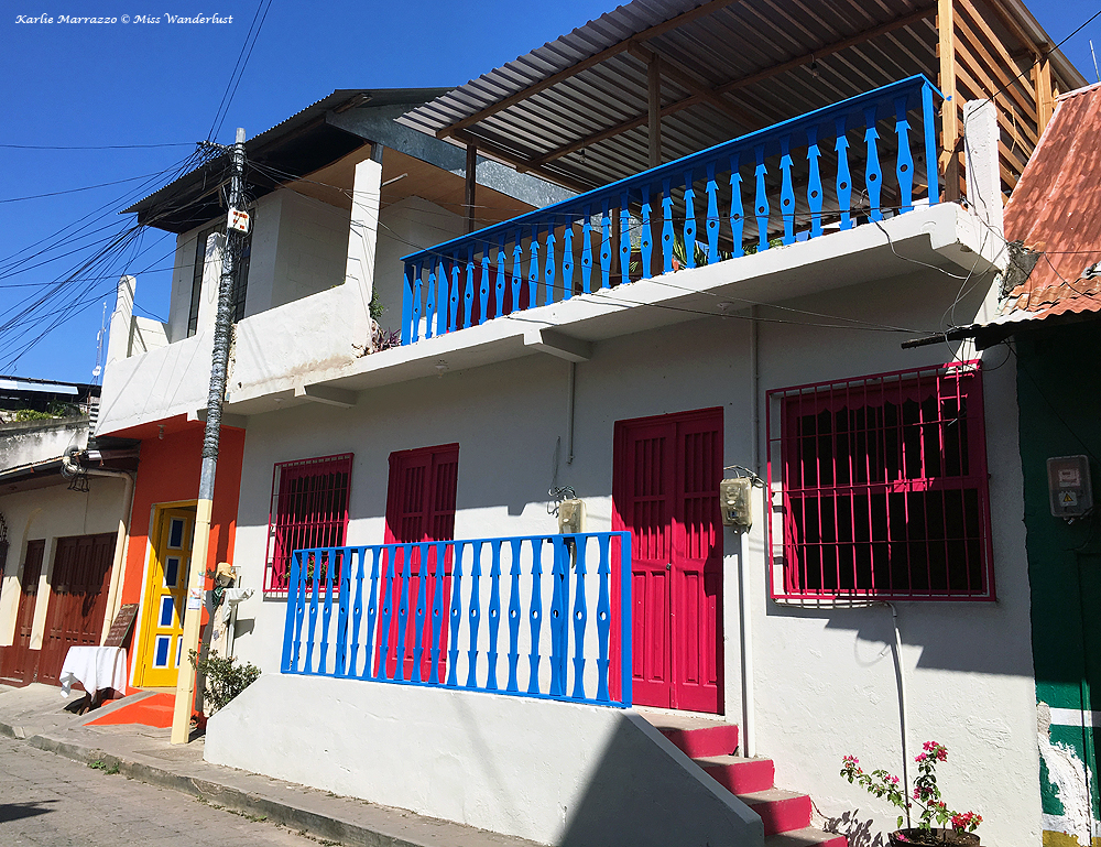 a bright white building with pink doors and blue railings