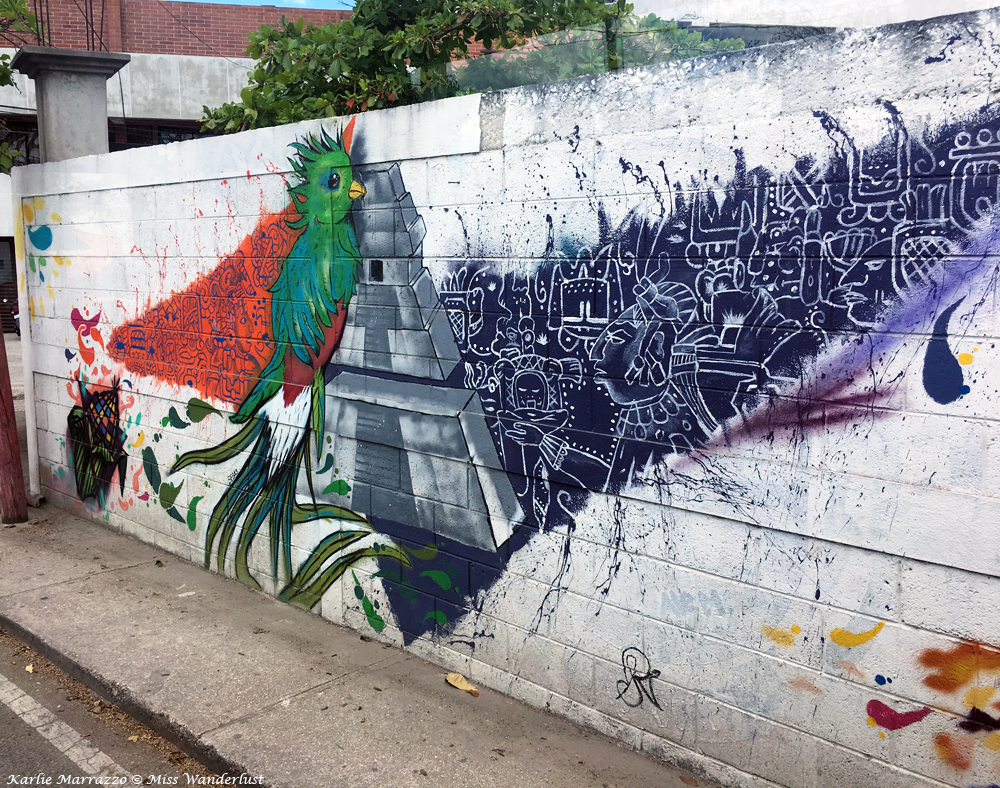 street art on a white brick wall portraying a mayan pyramid and a green bird