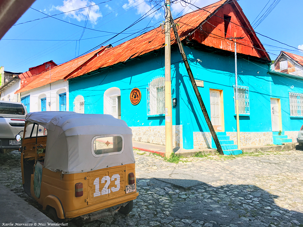 a street scene in guatemala, a cobblestone street, a bright blue building and a small orange bicitaxi