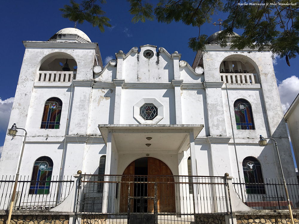 a white cathedral against a blue sky in flores, guatemala