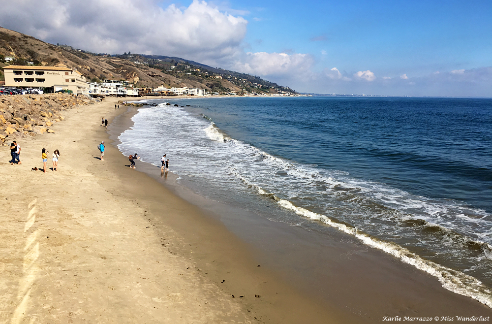 a panoramic view over malibu beach, showing a wide sandy beach, the ocean, and the sky with a few clouds