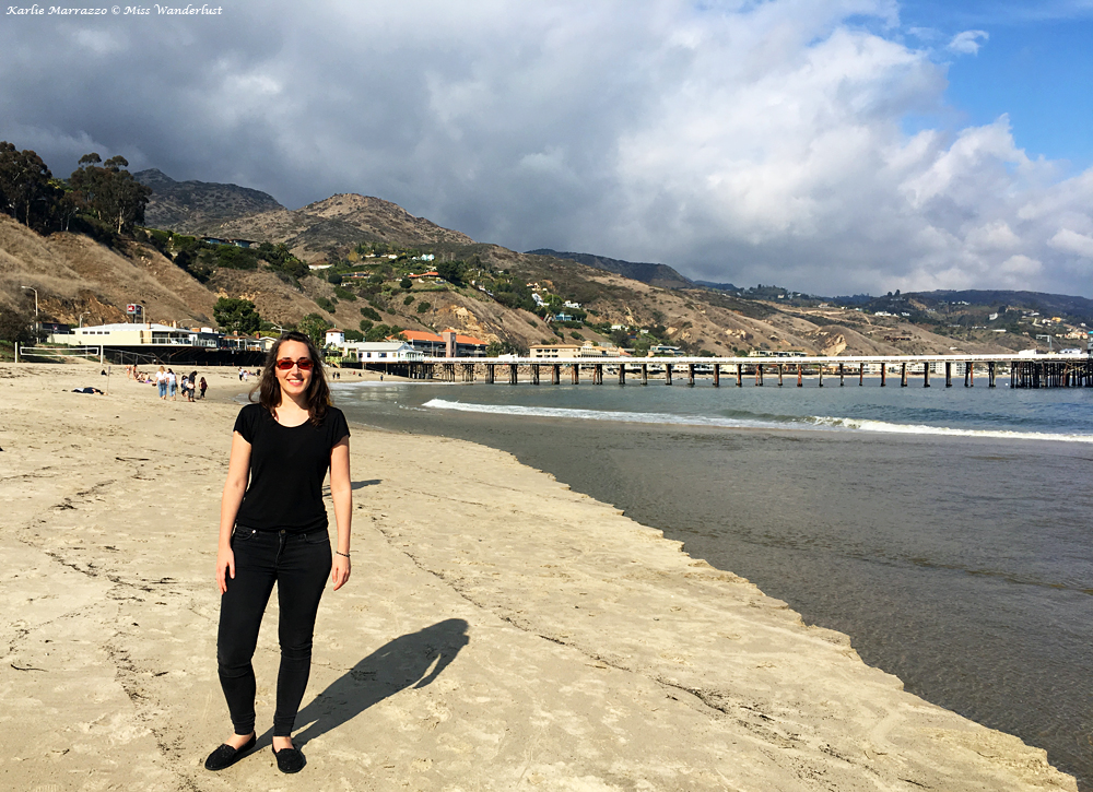 a young brunette woman wearing a black t-shirt and jeans stand smiling on malibu beach