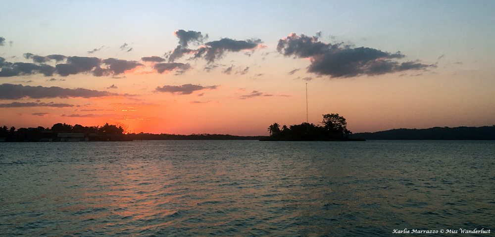 a pink sunset over a lake with a small island on the horizon