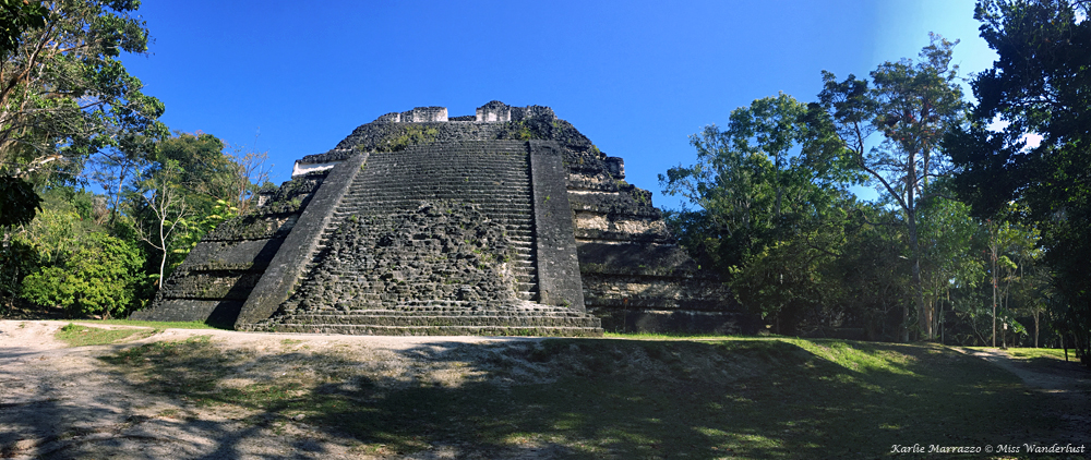 a mayan pyramid shown in full view against a blue sky