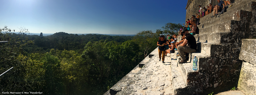 a group of people sit on the steps on top of an ancient mayan pyramid at tikal